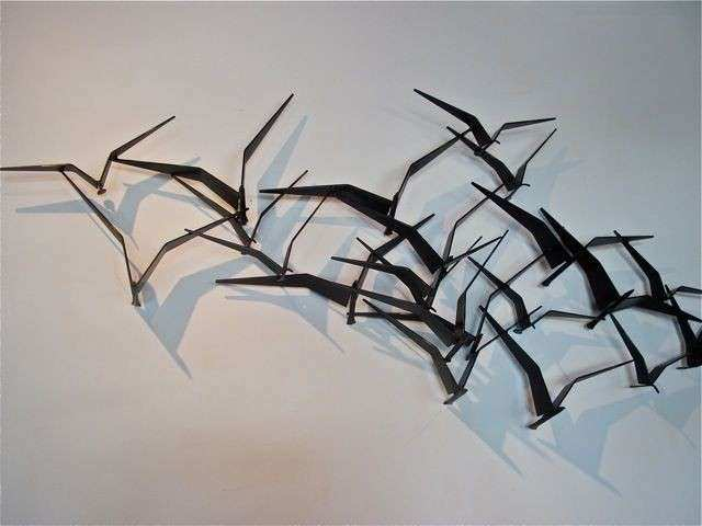 Metal sculpture bird formation inflight