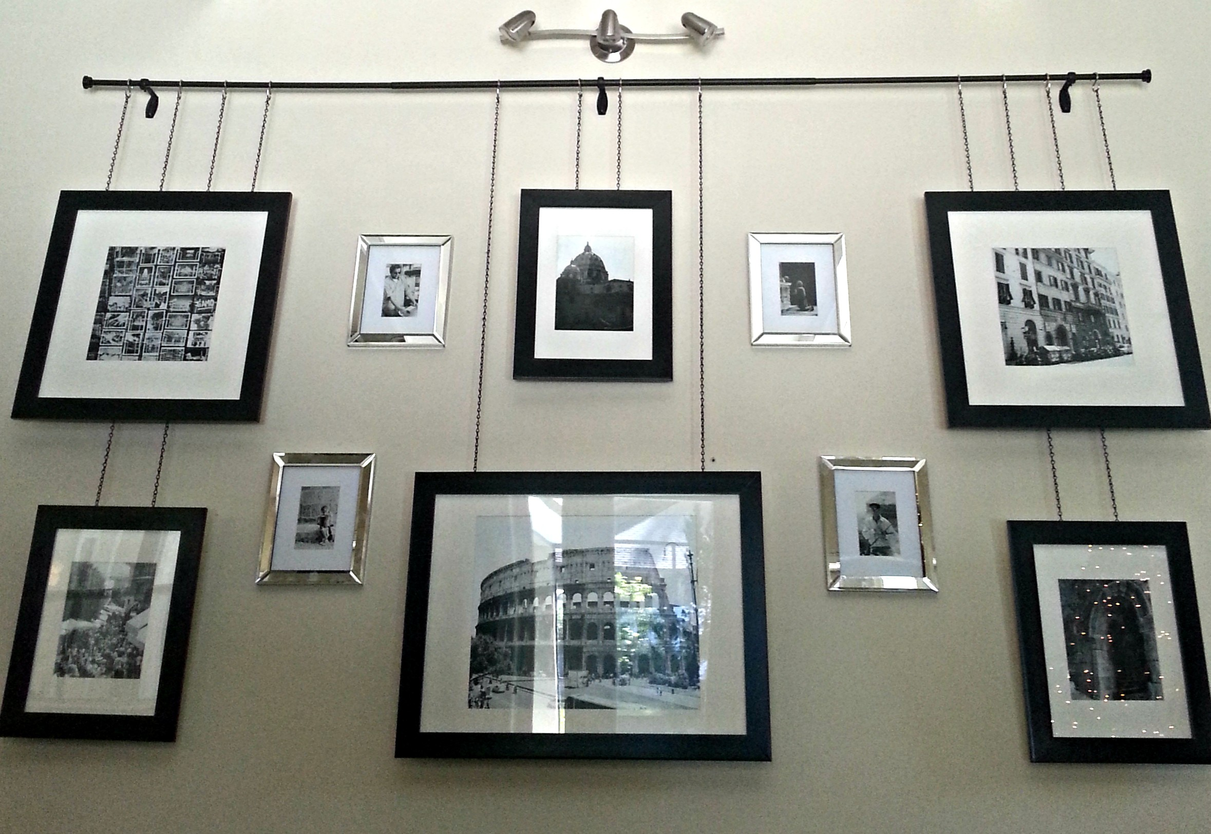 Gallery frames hanging by chain from a curtain rod with contrasting
