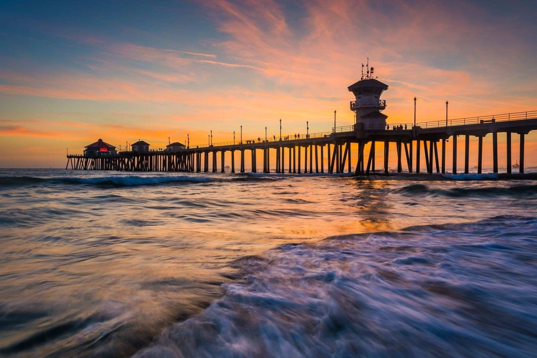 Waves in the Pacific Ocean and the pier at sunset in Huntington
