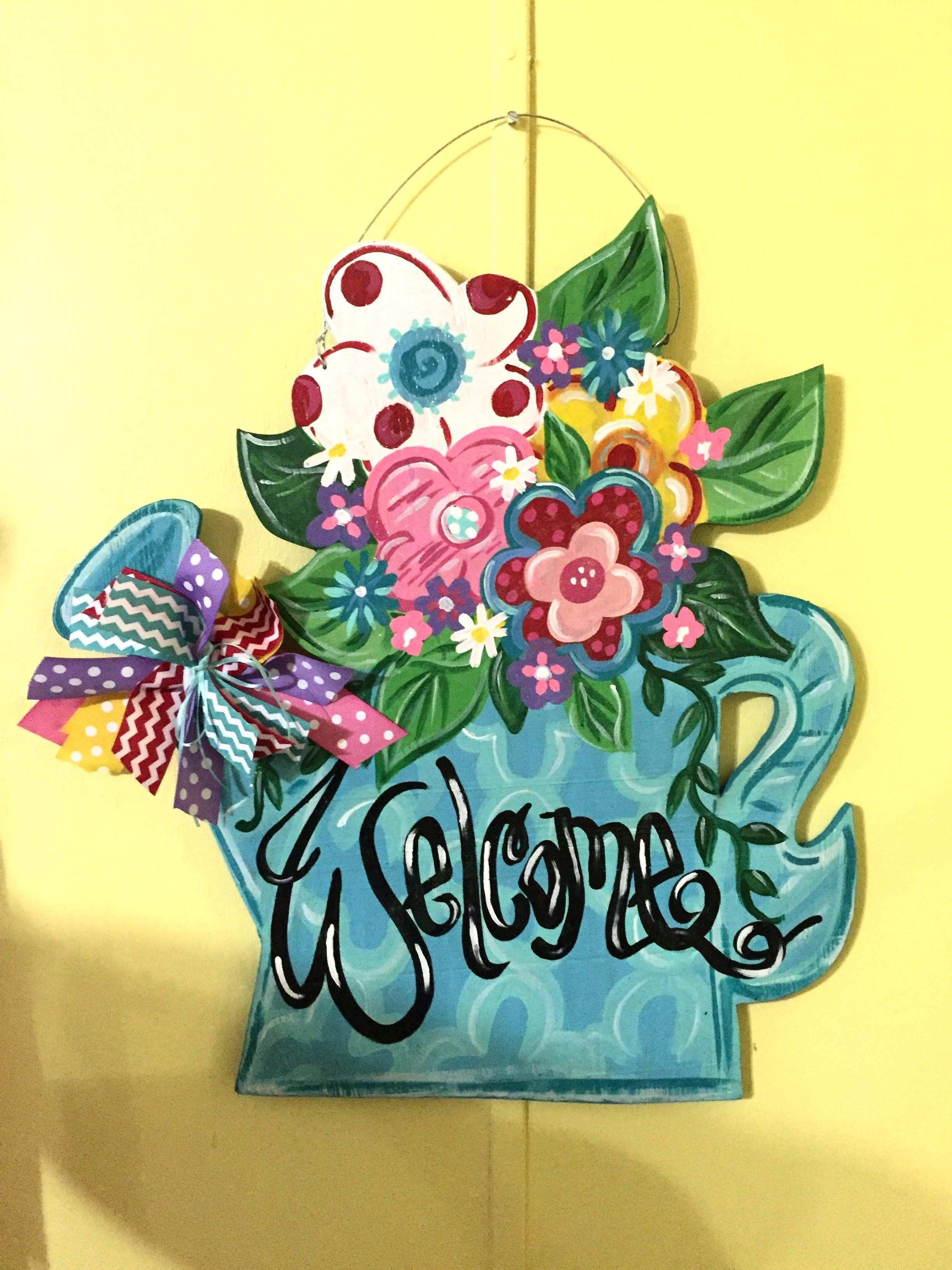 I painted this watering can door hanger for spring