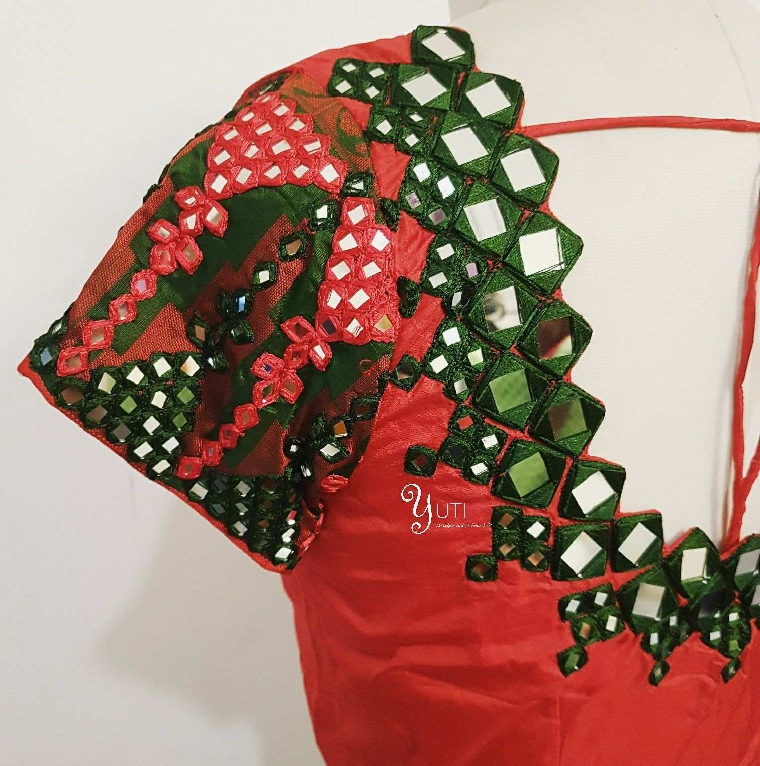 A plain red blouse decorated with mirror and threads at YUTI For