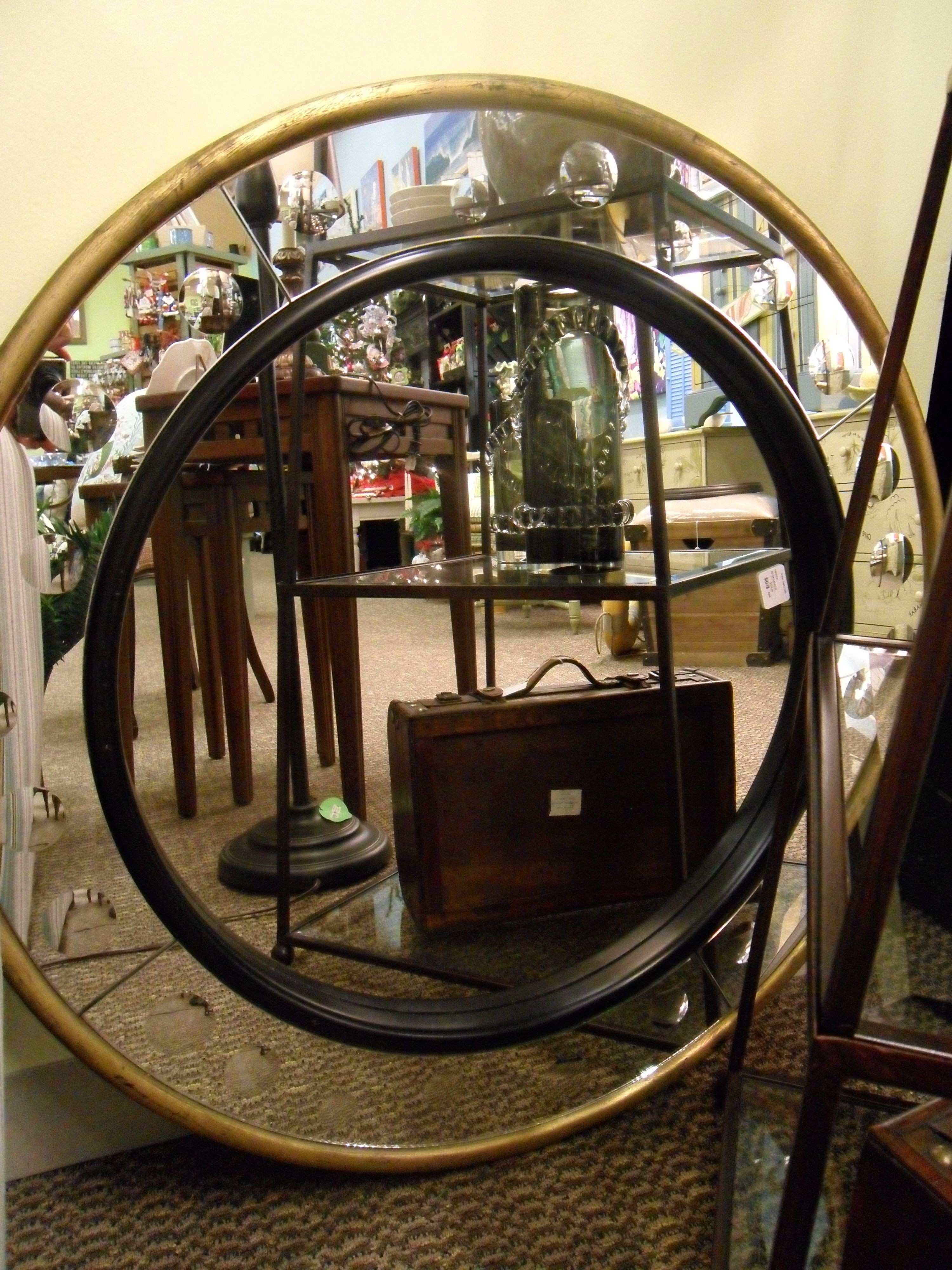 Round mirror with a black trim on the inside ring and a gold trim on