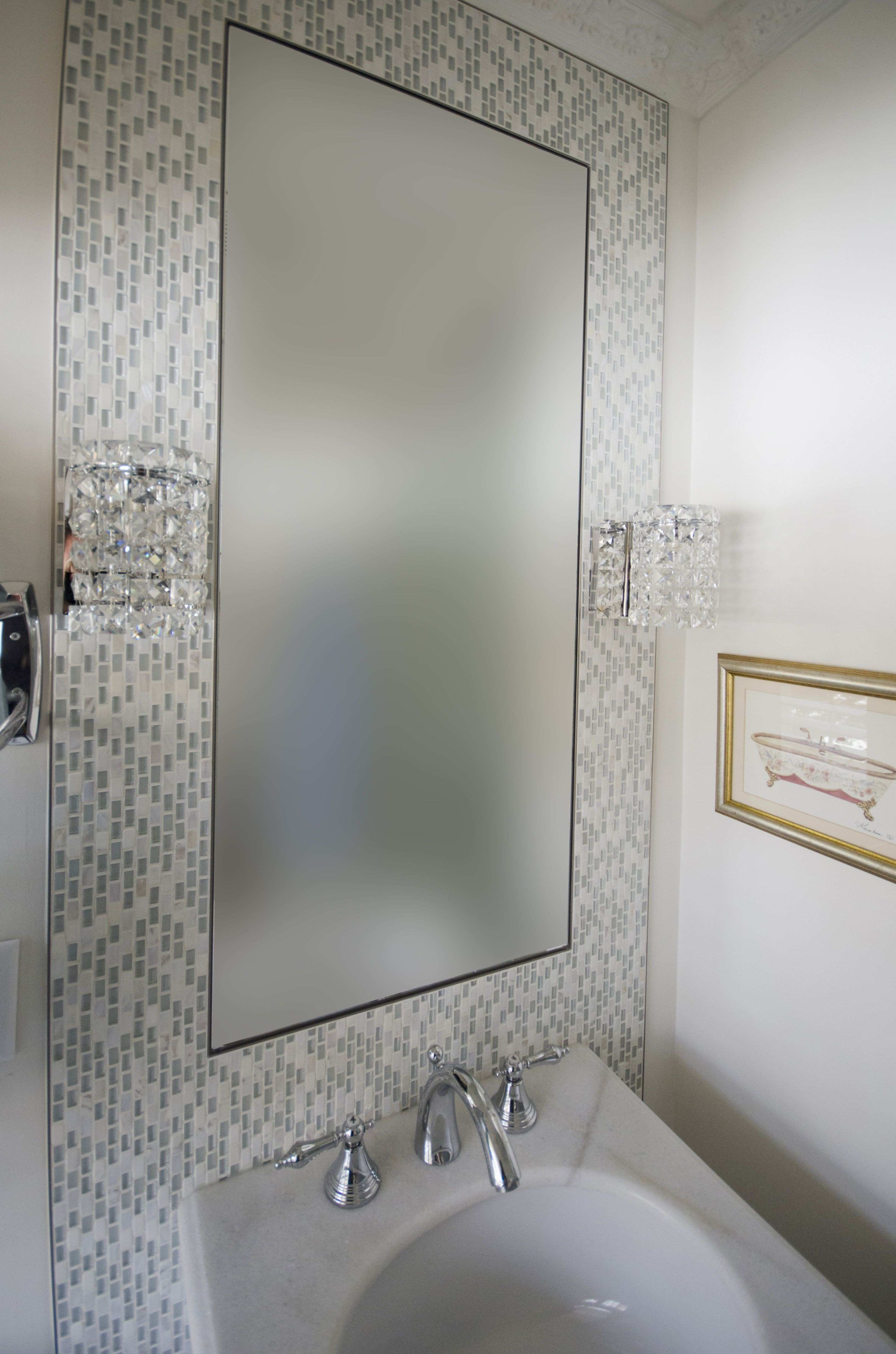 Vanity wall sconces installed on the mosaic mirror frame great for