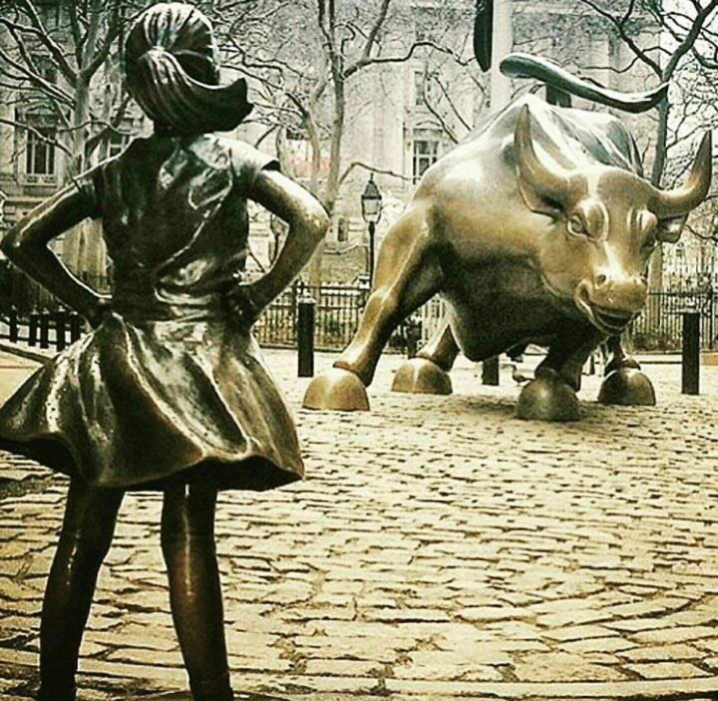 Fearless girl statue wall Street charging bull empowered strong